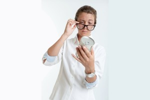 Young woman inspecting an aluminum can through her glasses